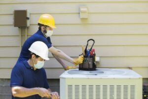 two-technicians-working-on-outside-ac-unit